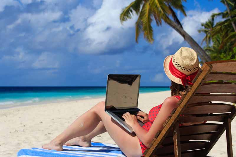 A lady with a laptop on the beach.
