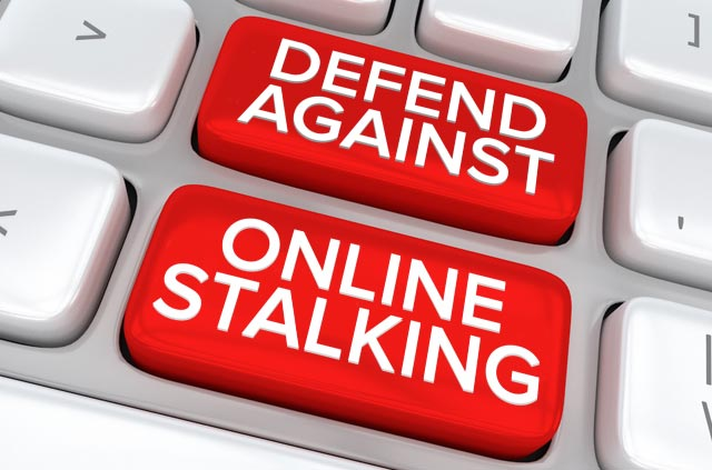 "Two computer keyboard keys with ""Defend against online stalking"" written on them."
