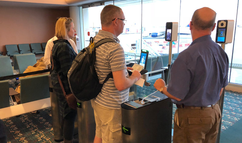 Travelers going through a facial recognition scanner.